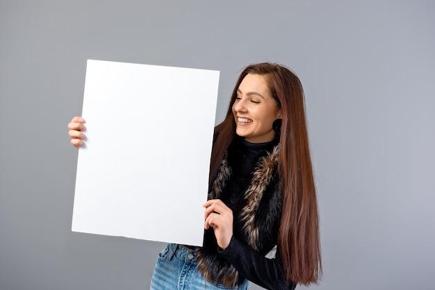 Emocjonalna młoda nastolatka kobieta pokazująca pusty szyld z miejscem na kopię, odizolowana na szaro