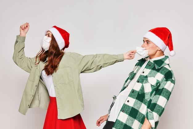 Emocjonalna młoda para boże narodzenie i nowy rok czapki medyczne maski wakacyjne