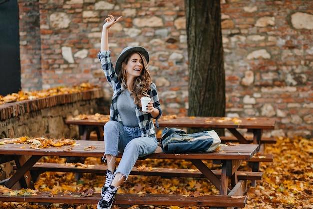 Emocjonalna modelka w krótkich dżinsach i czarnych butach pije kawę w parku w ciepły poranek września