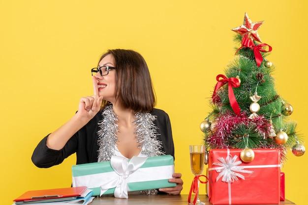 Emocjonalna nerwowa biznesowa dama w garniturze w okularach trzymająca prezent, wykonująca gest ciszy i siedząca przy stole z choinką w biurze