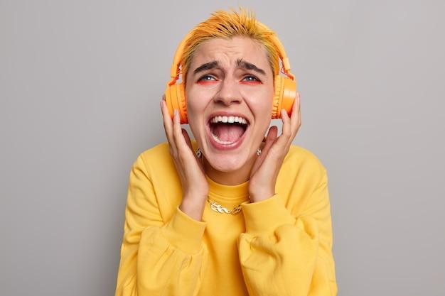 Emocjonalna niezadowolona stylowa punkowa kobieta z modną fryzurą głośno wykrzykuje trzyma ręce na słuchawkach nosi swobodny żółty łańcuszek sweter na szarej ścianie