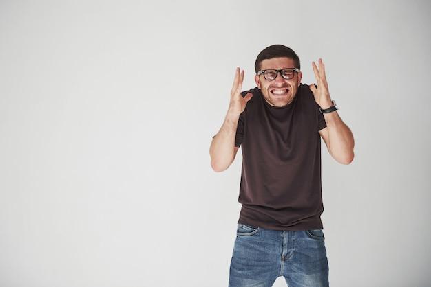 Emocjonalna osoba w zwykłym ubraniu i okularach wygląda na nieodwracalny błąd