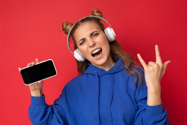 Emocjonalna pozytywna ładna młoda kobieta ubrana w stylową niebieską bluzę z kapturem na białym tle na czerwonym tle