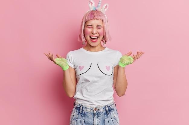 Emocjonalna, różowowłosa młoda azjatka rozkłada dłonie i głośno krzyczy ubrana w casualową koszulkę i dżinsy, ma jasny makijaż
