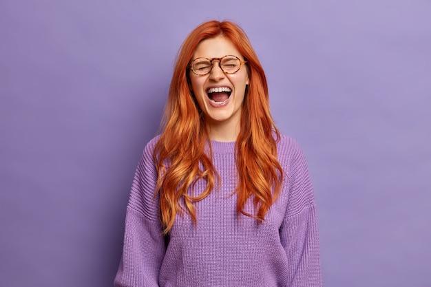 Emocjonalna ruda kobieta nie może przestać się śmiać, ma szeroko otwarte usta.