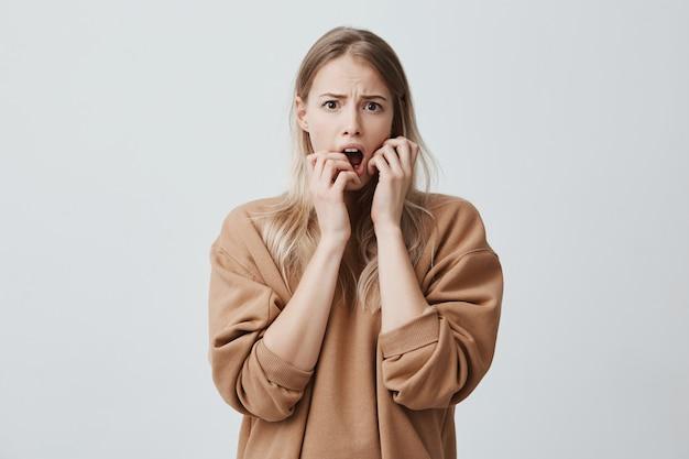 Emocjonalna śliczna kobieta o blond włosach, oszołomiona. negatywne emocje