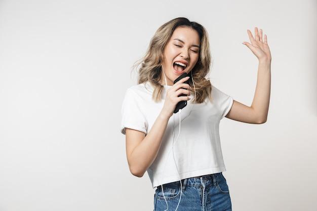 Emocjonalna śliczna młoda kobieta pozuje na białym tle nad białą ścianą śpiewając na ścianie, słuchając muzyki za pomocą słuchawek i telefonu komórkowego