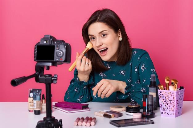 Emocjonalna śmieszna młoda kobieta siedzi przy stole z kosmetykami, strzelając do nowego bloga o makijażu dla swojego bloga, szeroko otwierając usta, trzymając w dłoni profesjonalny pędzel, ubrana w bluzkę z nadrukiem kwiatowym.