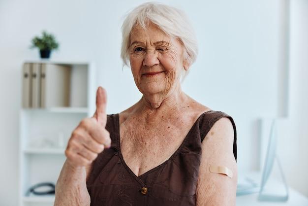 Emocjonalna starsza kobieta bandaid na ramieniu paszport szczepionkowy ochrona immunologiczna