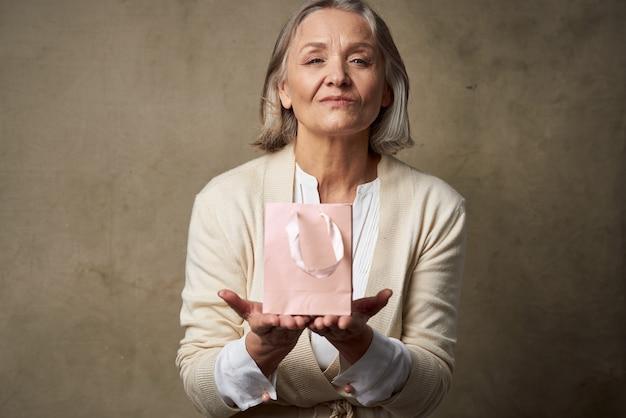Emocjonalna starsza kobieta w różowym pakiecie do pielęgnacji prezentów