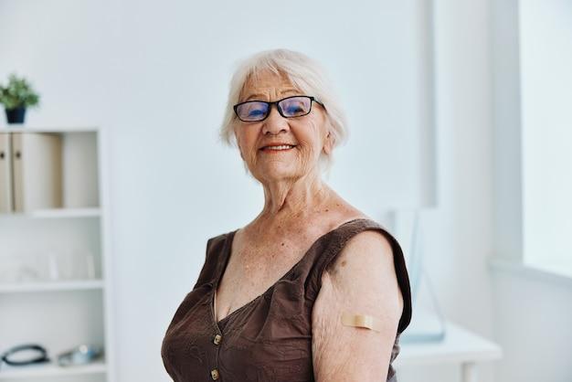 Emocjonalna starsza kobieta w szpitalu nosicielem bezpieczeństwa szczepień w paszporcie