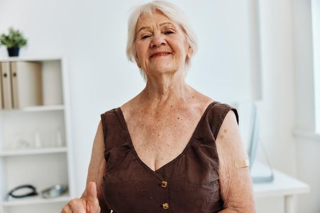 Emocjonalna staruszka z plastrem na ramieniu paszport szczepionkowy ochrona immunologiczna