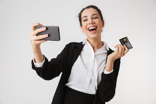 Emocjonalna szczęśliwa biznesowa kobieta zrobić selfie przez telefon trzymając kartę kredytową.