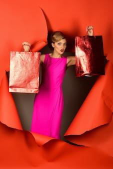 Emocjonalna szczęśliwa dziewczyna przebija się przez dziurę w czerwonym papierze. piękna blondynka w różowej sukience trzyma pakiety wakacyjne. promocja sklepu. sklep reklamowy. modne ubrania. produkty modowe.