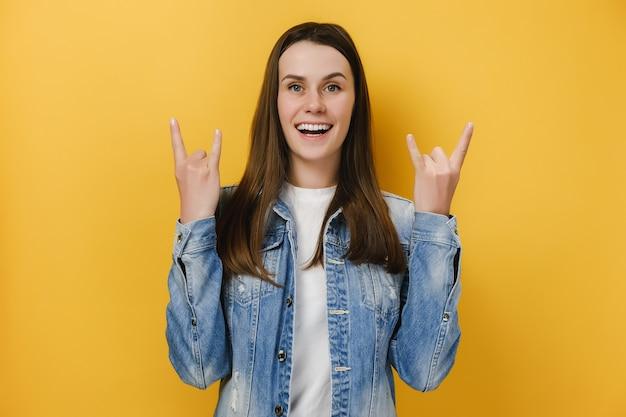 Emocjonalna szczęśliwa kobieta pokazuje gest rock n rolla