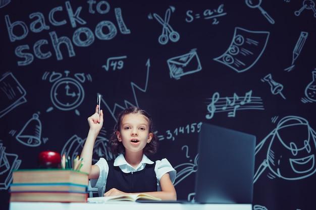 Emocjonalna uczennica podnosi rękę z piórem siedzącym z edukacją na odległość na laptopie