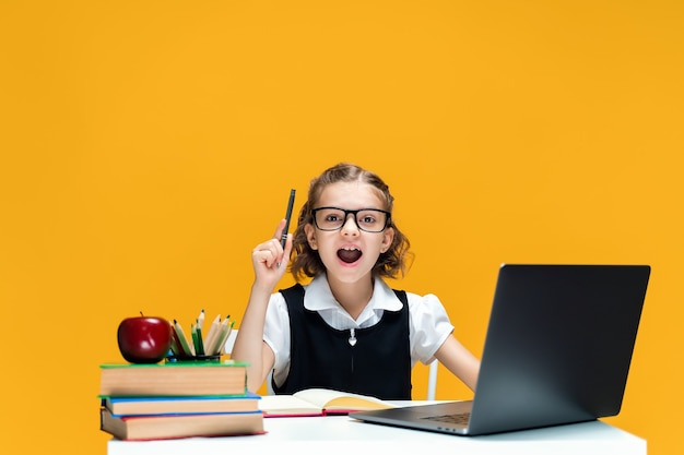 Emocjonalna uczennica w okularach podnosząca pióro do góry siedząca przy biurku z edukacją na odległość na laptopie