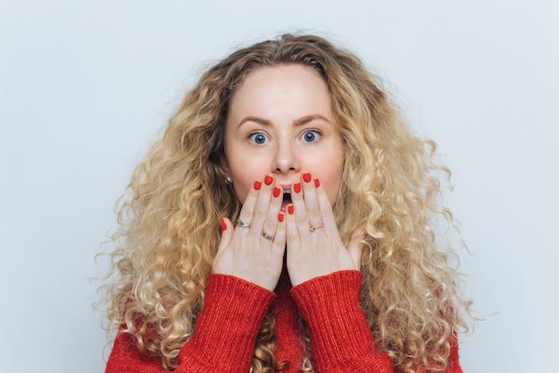 Emocjonalna urocza kobieta o nieoczekiwanym wyglądzie zakrywa usta dłonią