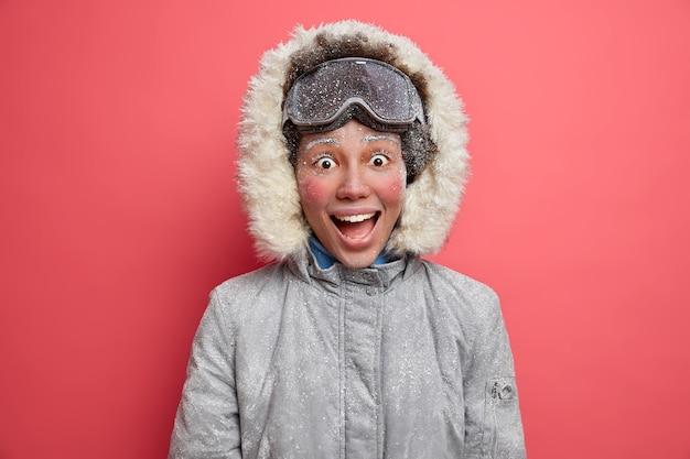 Emocjonalna, wesoła zimowa dziewczyna wygląda z radosnym wyrazem, ma czerwoną twarz pokrytą szronem, lubi jeździć na snowboardzie zimą, nosi ciepłą kurtkę.