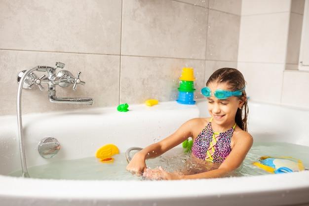 Emocjonalna zabawna kaukaska dziewczyna radośnie bawi się wodą podczas kąpieli w łazience. pojęcie rozrywki i higieny zdrowych dzieci. copyspace