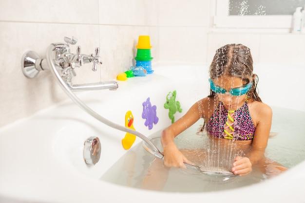 Emocjonalna zabawna kaukaska dziewczyna radośnie bawi się wodą podczas kąpieli w łazience
