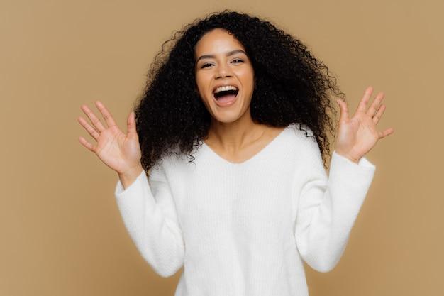 Emocjonalna zadowolona afroamerykanka o kruchych czarnych włosach, aktywnie podnosi ręce i gesty