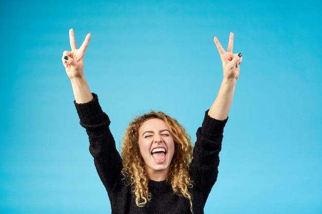 Emocjonalna zadowolona młoda atrakcyjna imbirowa kędzierzawa kobieta z otwartymi ustami świętuje i kibicuje sukcesowi podnosząc ręce
