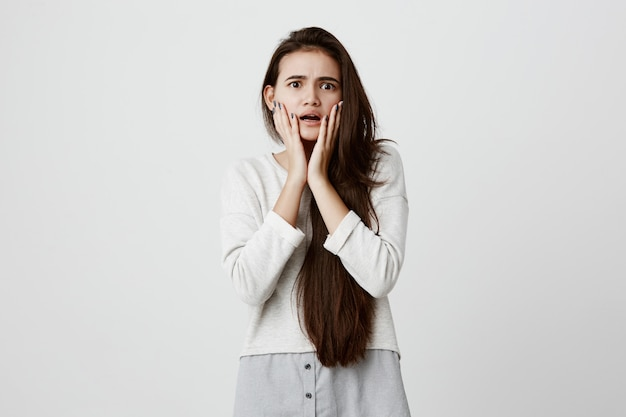 Emocjonalna zmartwiona brunetka trzyma ręce na policzkach, otwiera usta, czuje się zakłopotana i sfrustrowana po tym, jak wyszła z domu bez odłączonego żelazka. ludzkie emocje i uczucia