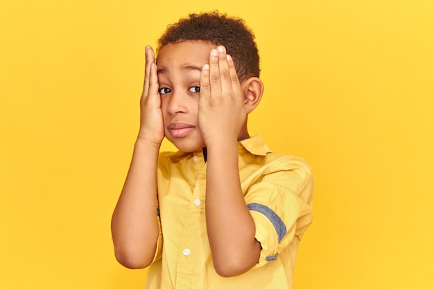 Emocjonalne, ciemnoskóre dziecko trzymające ręce na policzkach, zdenerwowane, zapominalskie spojrzenie, zestresowane z powodu złych ocen w szkole.