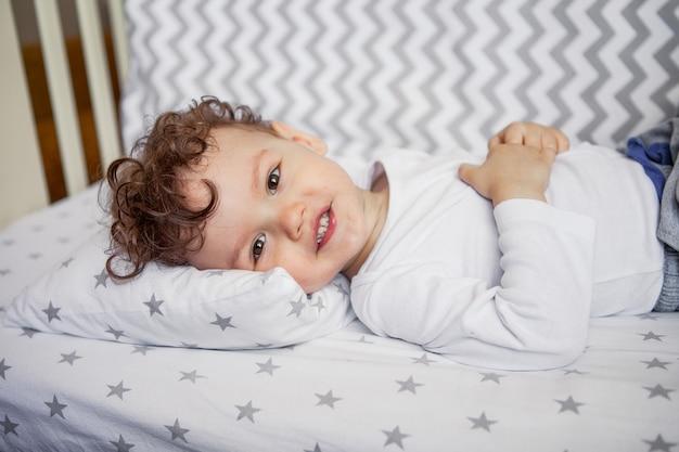 Emocjonalne dziecko leży w łóżeczku. zdrowy sen. zasypiam.