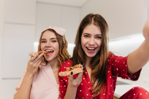 Emocjonalne kręcone dziewczyna jedzenie pizzy z uśmiechem. wewnątrz zdjęcie zadowolonej brunetki kobiety w czerwonej piżamie robi selfie z przyjacielem.