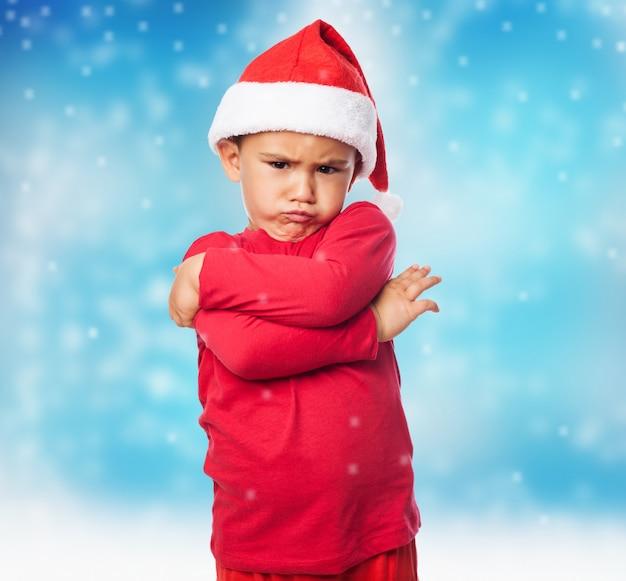 Emocjonalne mały chłopiec z santa kapelusz