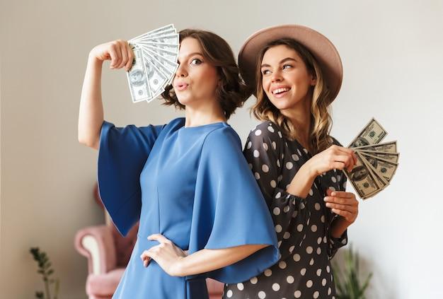 Emocjonalne młode kobiety indoors trzyma pieniądze.