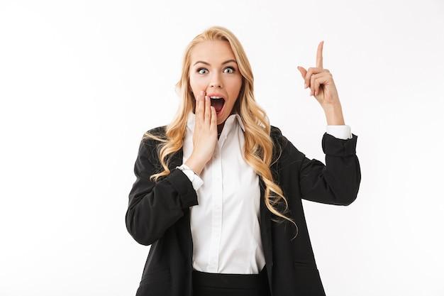 Emocjonalne podekscytowany biznes kobieta pozowanie na białym tle nad białą ścianą wskazując.