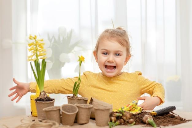 Emocjonalne szczęśliwe dziecko ogrodnicze wiosenne kwiaty z narzędziami, rękawiczki ogrodnicze, ziemia doniczkowa