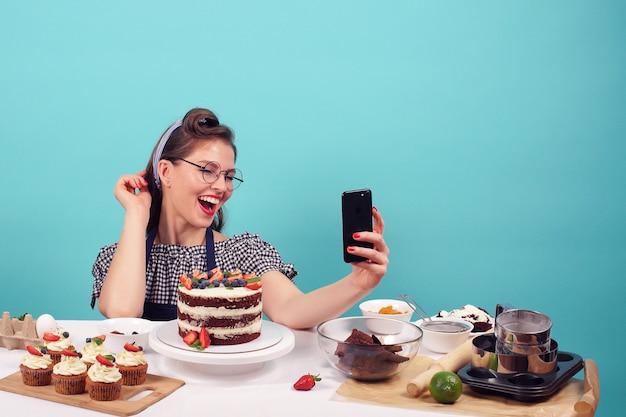Emocjonalne wesoły brunetka ciasto sprawia, że selfie w studio na na białym tle