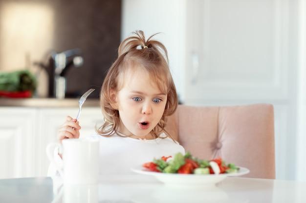 Emocjonalne wyrażenie dziecko dziewczynka jedzenie świeżych surowych warzyw sałatka witaminowa w białej kuchni. koncepcja zdrowej żywności dla dzieci