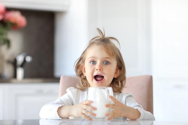 Emocjonalne wyrażenie dziecko dziewczynka otwarte usta z wąsem mleka na ustach trzymając szklankę mleka. białe światło kuchnia z tłem kwiatów. mleko, nabiał, wapń dla dobrego zdrowia dzieci