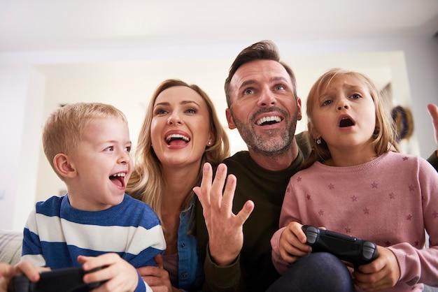 Emocjonalni rodzice i dzieci grające w gry wideo w domu