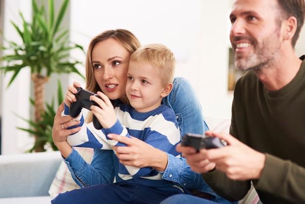 Emocjonalni rodzice i syn grają w gry wideo