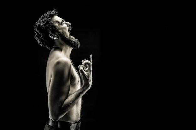 Emocjonalnie ekspresyjne zdjęcie wrzeszczącego brodatego mężczyzny, wściekły płacz z bólu czarno-biały