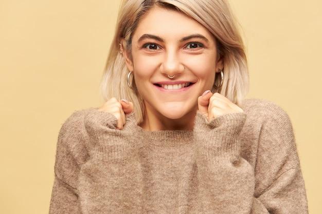 Emocjonalnie ekstatyczna, urocza młoda kobieta z blond fryzurą i kolczykiem w nosie wykrzykuje podekscytowany, radosny wygląd, wiwatowanie, radowanie się z sukcesu, patrzenie z szerokim promiennym uśmiechem, gryzienie warg