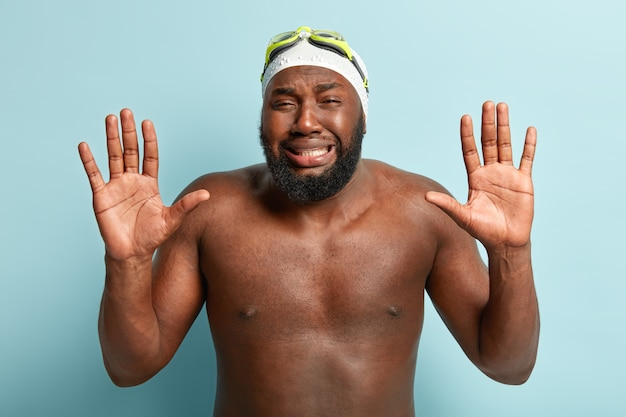 Emocjonalnie niezadowolony afroamerykanin pokazuje dłonie, płacze z rozpaczy, ma ponury wyraz twarzy, nagi tors
