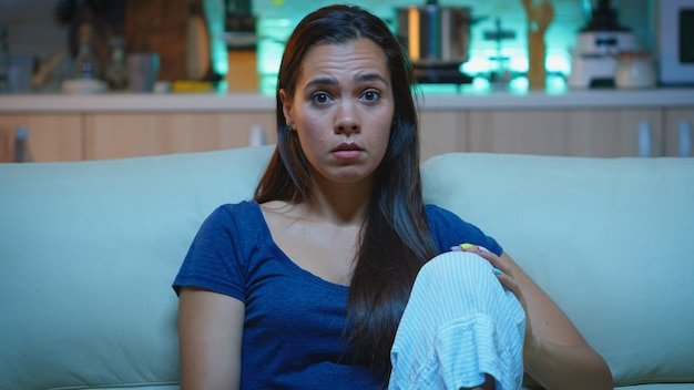 Emocjonalnie oszołomiona i szerokooka kobieta reagująca na imponujący i zaskakujący moment w telewizji. zszokowana skoncentrowana pani jedząca popcorn i samotnie oglądająca serialowy dom późną nocą.