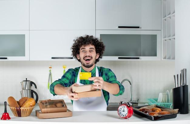 Emocjonalnie pozytywny młody człowiek stojący za stołem z różnymi wypiekami i trzymający brązowe pudełka na karty bankowe w białej kuchni