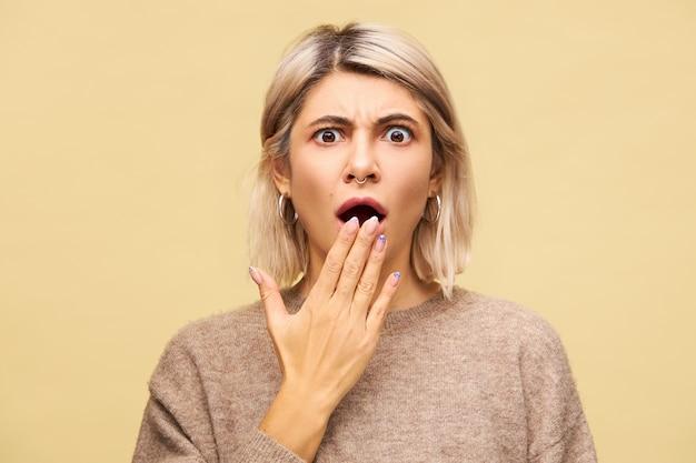 Emocjonalnie przerażona przerażona młoda kobieta o blond włosach pozująca odizolowana, sparaliżowana strachem, przerażeniem, wydająca zduszony krzyk, zakrywająca otwarte usta, otrzymująca złe wieści