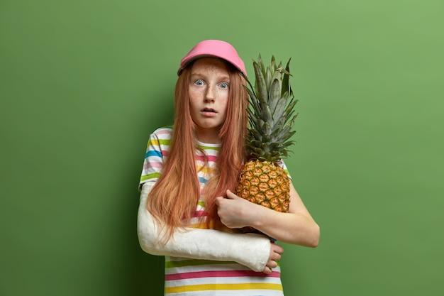 Emocjonalnie przestraszona piegowata dziewczyna obejmuje ananasa, lubi owoce tropikalne, nosi czapkę i koszulkę w paski, ma złamaną rękę, odizolowaną na zielonej ścianie. koncepcja dzieciństwa i stylu życia