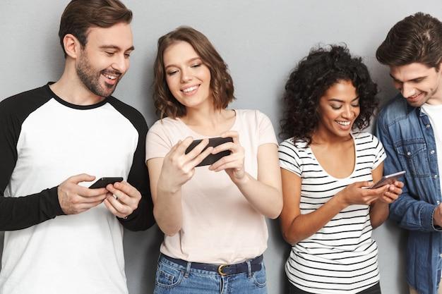 Emocjonalnie wesoła grupa przyjaciół korzystających z telefonów komórkowych, spoglądających na bok.