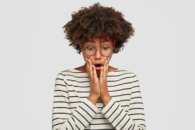 Emocjonalnie zaskoczona afroamerykanka ze zdumioną miną, trzyma obie dłonie na policzkach