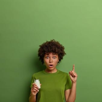 Emocjonalnie zaskoczona, kręcona młoda kobieta wskazuje palcem wskazującym w górę, pokazuje coś niesamowitego powyżej, pozuje z jogurtem, ma prawidłowe odżywianie, przestrzega zdrowej diety, ubrana w jaskrawozieloną koszulkę